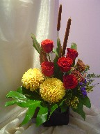 Roses, commercial mums, cattails, celosia, waxflowers, monstera, and cordeline