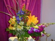 Dendrobium orchids, iris, coffee beans, lillies, alstroemeria, solidago, seed eucalyptus, and monstera