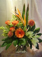 Bird of paradise, dahlia, roses, gerbera, lillies, solidago, and fatsia japonica