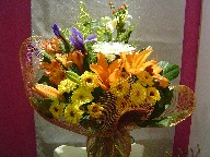Iris, gerbera, alstroemeria, daisies, lillies, solidago, and coffee beans
