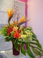 Cymbidium orchids, solidago, coffee beans, pine, lillies, roses, bird of paradise, and monstera