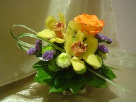 Cymbidium orchids, rose, pompoms, statice, and monkey grass