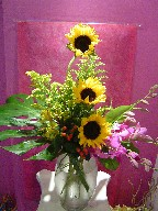 Sunflowers, coffee beans, solidago, orchids, alstroemeria, and monstera