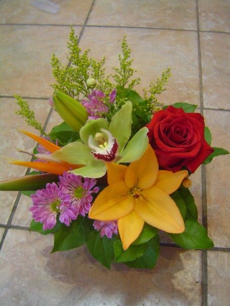 Bird of paradise, rose, cymbidium orchid, lilies, daisies, and solidago