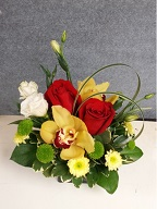 Cymbidium orchids, roses, lisianthus, pompoms, monkey grass and variegated pitt