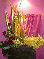 Heliconia, roses, celosia, cymbidium orchids, zebra leaves, and tea leaves