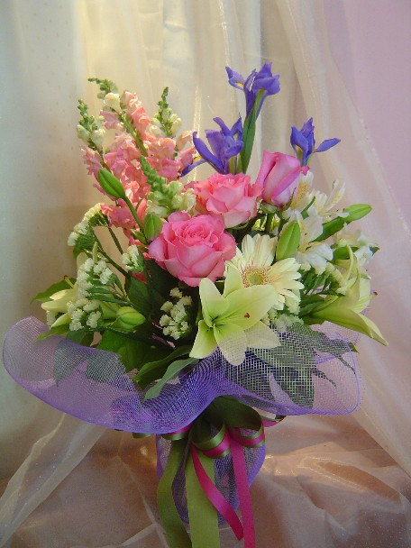 Roses, gerbera, lillies, iris, snapdragon, statice, and alstroemeria