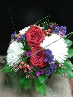 Roses, spider mums, statice, hypericum, waxflowers, and steel grass