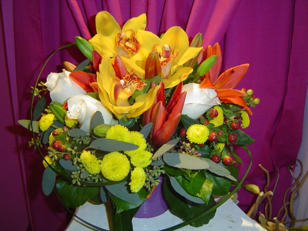 Cymbidium orchids, roses, pompoms, seed eucalyptus, lilies, hypericum, and monkey grass