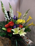 Calla lillies, asiatic lillies, iris, roses, snapdragon, monstera, and monkey grass