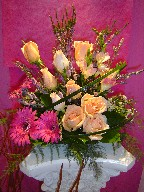 Heather, gerbera, roses, freesia, waxflowers, and monkey grass