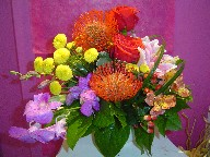 Protea, roses, lillies, orchids, pompoms, alstroemeria, coffee beans, solidago, monkey grass, and variegated pitt