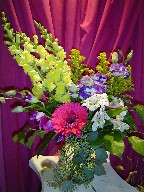 Gerbera, snapdragon, alstroemeria, solidago, lisianthus, orchids, and seed eucalyptus