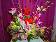 Roses, orchids, lillies, alstroemeria, waxflowers, and monkey grass