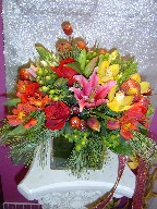 Roses, Christmas ornament, Star of Bethlehem, green berries, cymbidium orchids, tulips, lillies, alstroemeria, and pine