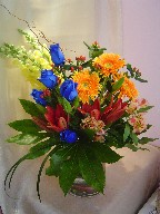 Roses, snapdragon, gerbera, lilies, alstroemeria, curly willow, hypericum, and fatsia japonica