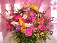 Yellow calla lillies, heather, gerbera, hot pink roses, mimosa, and tulips in a basket arrangement