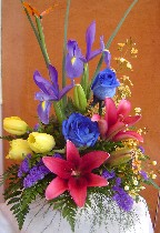 Yellow tulips, irises, blue roses, tiger lillies, waxflowers, and statice