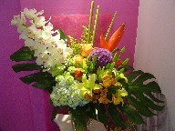 Cymbidium orchids, monstera, heliconia, allium, solidago, hydreangea, lillies, alstroemeria, roses, and pompoms