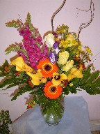 Snapdragon, calla lillies, roses, lithianthus, coffee beans, helenium, philodendron, and curly willow