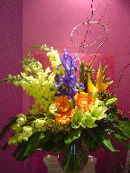 Snapdragon, iris, coffee beans, gerbera, lillies, cymbidium orchids, heliconia, monstera, and curly willow