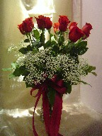 Dozen red roses with baby's breath in a vase
