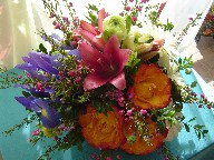 Iris, boronia, daisies, ranunclus, pink lilies and circle roses in a basket