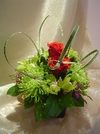 Roses, cymbidium orchids, spider mums, waxflowers, and monkey grass