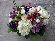 Cymbidium orchids, hydreangeas, roses, lisianthus, tinted commercial mums, alstroemeria, and pandanas leaves