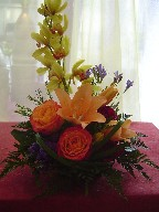 Mini cymbidium, statice, orange lillies, and circus roses