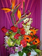 Bird of paradise, roses, gerbera, alstroemeria, lillies, coffee beans, monkey grass, and cymbidium and dendrobium orchids