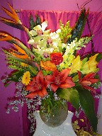 Calla lillies, cymbidium orchids, bird of paradise, snapdragon, sago palm, eucalyptus, gerbera, aspedestra, roses, lillies, and curly willow