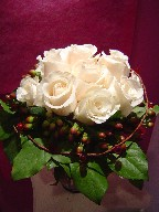 Cream roses and red berries in a vase