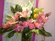 Cymbidium orchids, roses, lillies, solidago, sago palm, monstera, stock, and heather