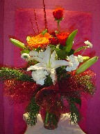 Lillies, carnations, roses, gerbera, aster, pine, and Christmas branch