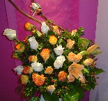 Cream, orange, and circus roses, berries, and tiger lillies in a basket