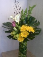 Bells of Ireland, calla lillies, gerberas, roses, cymbidium orchids, asiatic lillies, monstera, and branch