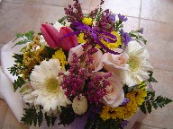 White gerbera, tulips, heather, button daisies, casiomoto, waxflowers, and anna roses in a basket