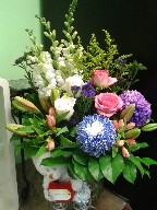 Commercial mums, snapdragon, roses, alstroemeria, lillies, statice, and solidago