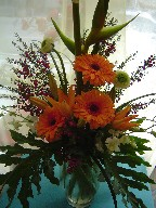 Gerberas, heliconia, ranunclus, boronia, pink and white orchids, asiatic lilies, and philodendron leaves in a vase