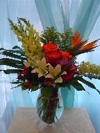 Bird of paradise, snapdragon, roses, gerbera, lillies, orchids, coffee beans, gerbera, and monstera