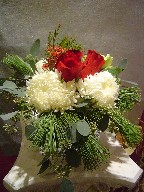 Roses, commercial mum, alstroemeria, pine, waxflowers, and seed eucalyptus